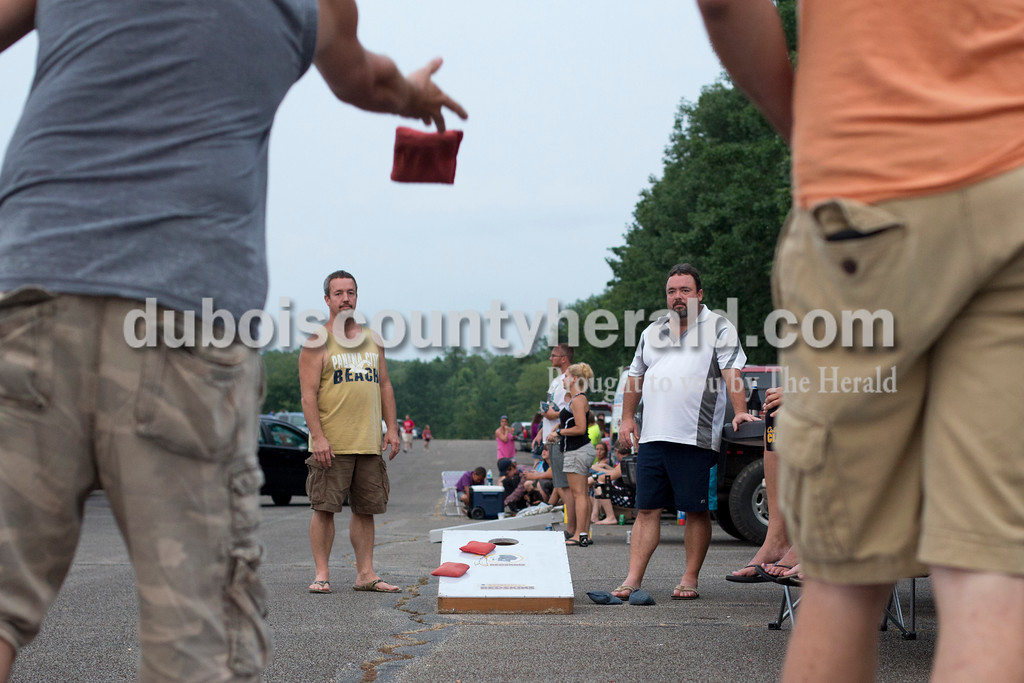 Erica Lafser/The Herald<br /> Aaron Schipp of Jasper, far left, played corn hole with friends Steve Mattingly of Lincoln City, left, Robert Mattingly of Jasper, right, and Kyle Griffith of Dubois, far right, on Saturday evening at Patoka Lake for Thunder Over Patoka. Since the beach at Patoka Lake flooded, everyone was relocated to a higher parking lot.