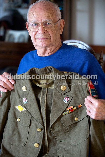 Rachel Mummey/The Herald<br /> World War II veteran Otto Begle of Ferdinand held up the jacket he wore as a member of the Military Police after being drafted in the army in 1945. Begle said he part of the largest draft group from Dubois County with 71 others. Since his service, he joined the Rifle Squad with the Ferdinand American Legion and has attended over 200 military funerals.