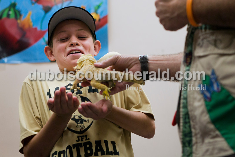 """Rockne Lueken of Jasper, 10, leaned back as """"Amazon John"""", John Cusson, showed him a bearded dragon lizard during the Silly Safaris event on Tuesday afternoon at the Jasper Public Library. <br /> Alisha Jucevic/The Herald"""