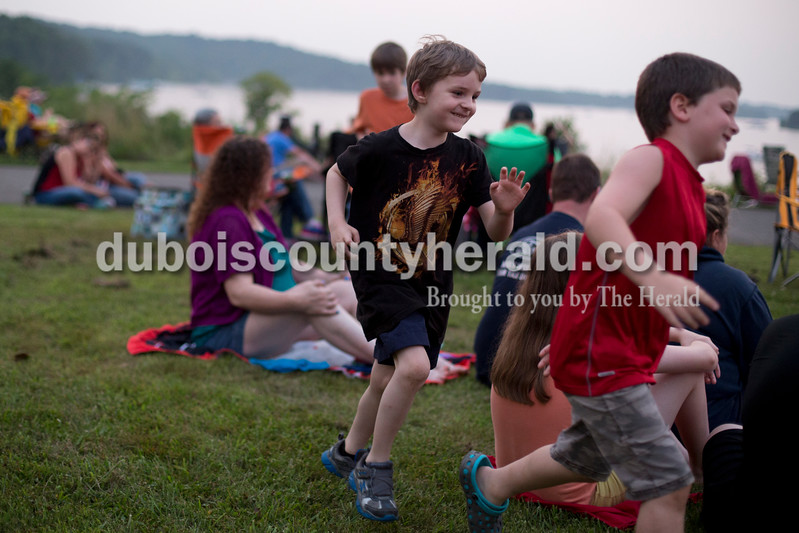 Erica Lafser/The Herald<br /> Sean Mills of Evansville, 6, left, played tag with his friend Jackson Hughes of Salem, Illinois, 7, right, and his brother Ben Mills of Evansville, 7, not pictured, on Saturday evening at Patoka Lake for Thunder over Patoka. Since the beach at Patoka Lake flooded, everyone was relocated to a higher parking lot.