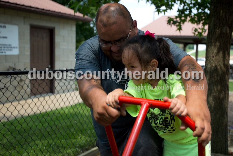 Erica Lafser/The Herald<br /> Jaime Moya of Birdseye helped his daughter Shaylee Moya of Texas, 4, play on the seesaw on Sunday at Birdseye Park.