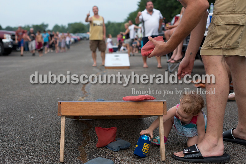Erica Lafser/The Herald<br /> Bristol Griffith of Dubois, 1, reached for her dad's drink while he played corn hole with his friends on Saturday evening at Patoka Lake for Thunder Over Patoka. Since the beach at Patoka Lake flooded, everyone was relocated to a higher parking lot.