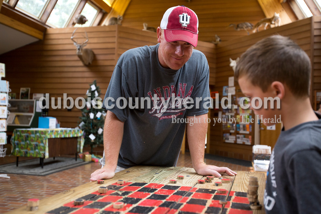Erica Lafser/The Herald<br /> Scott Hagan of Jasper, left, played checkers with his nephew Jackson Lambert of Brownsburg, 7, right, on Sunday during the Patoka Lake's Pirate Day Celebration at the Patoka Lake Nature Center. The pirate activities were supposed to take place at the beach, but since it was flooded they had to relocate to the nature center.