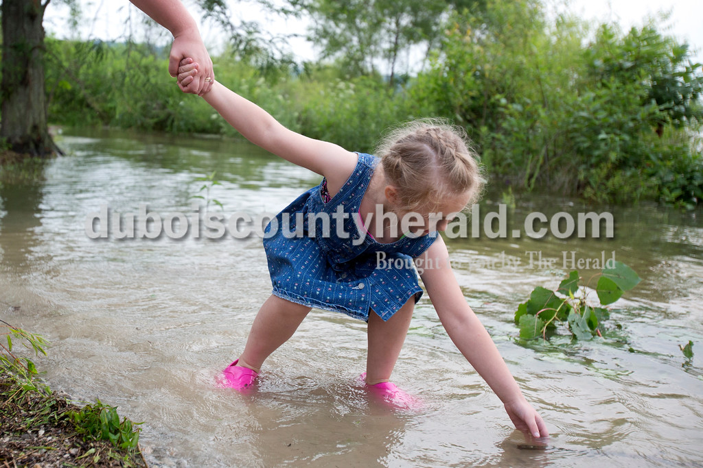 Erica Lafser/The Herald<br /> Stacy Merkley of Cannelton held the hand of her niece April Johnson of Cannelton, 6, while she reached for a stick in the water of the flooded parking lot next to the beach at Patoka Lake on Saturday evening for Thunder over Patoka. Since the beach at Patoka Lake flooded, everyone was relocated to a higher parking lot.