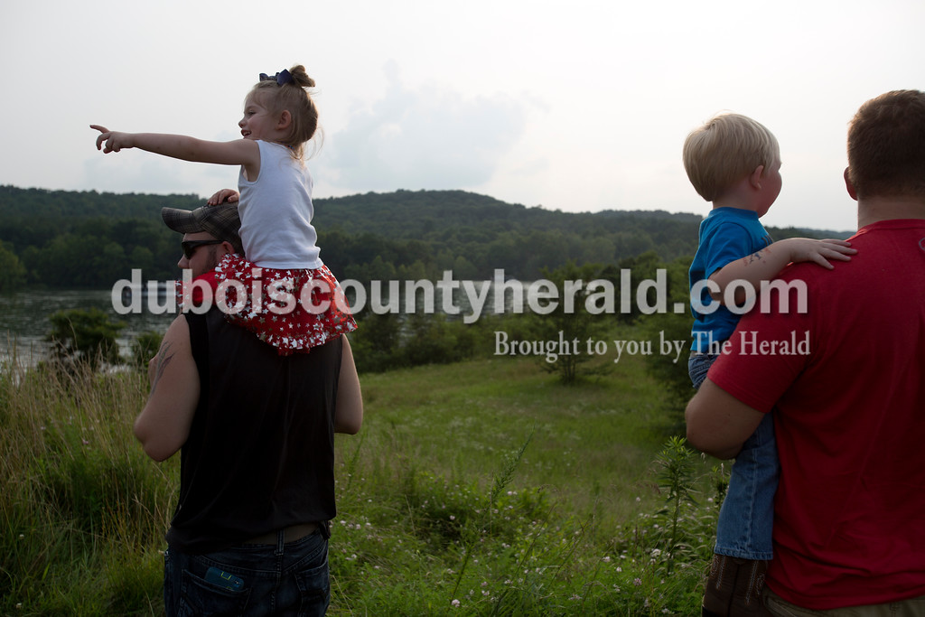 Erica Lafser/The Herald<br /> Andrew Miller of Dale held his daughter Jayla Miller of Dale, 3, left, on his shoulders next to Ryan Stalcup of Petersburg who held his son Cooper Stalcup of Petersburg, 3, right, while they waited for the fireworks to start on Saturday evening at Patoka Lake for Thunder Over Patoka. Since the beach at Patoka Lake flooded, everyone was relocated to a higher parking lot.