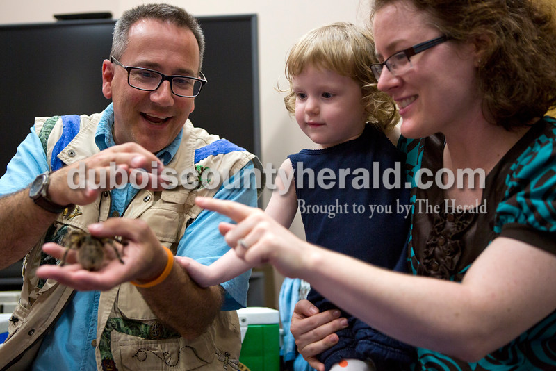 """John Cusson, """"Amazon John"""", showed Carleigh Price, 3, and her mother Amy, both of Huntingburg, a thin tendril of webbing from a tarantula during the Silly Safaris event on Tuesday afternoon at the Jasper Public Library. <br /> Alisha Jucevic/The Herald"""
