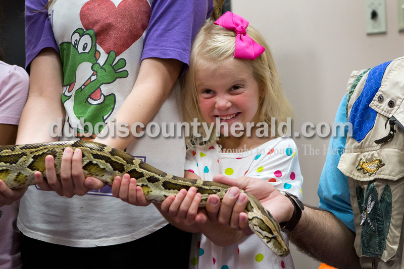 Adalyn Welp of Jasper, 5, made a face at her mother as she held a Burmese python during the Silly Safaris event on Tuesday afternoon at the Jasper Public Library. <br /> Alisha Jucevic/The Herald