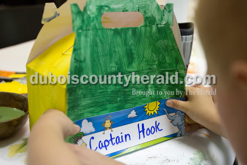 Erica Lafser/The Herald<br /> Andrew Smith of Corydon helped his son Gunner Smith of Corydon, 5, put a name tag on his painted treasure chest on Sunday during the Patoka Lake's Pirate Day Celebration at the Patoka Lake Nature Center. These pirate activities were supposed to take place at the beach, but since it was flooded they had to relocate to the nature center.