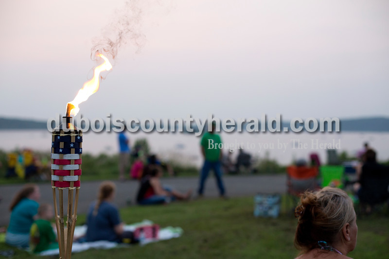 Erica Lafser/The Herald<br /> Tammy Goble of Warsaw sat near tiki torches on Saturday evening at Patoka Lake for Thunder over Patoka. Since the beach at Patoka Lake flooded, everyone was relocated to a higher parking lot.