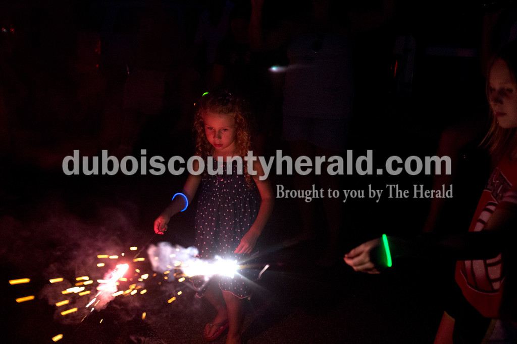Erica Lafser/The Herald<br /> Aryssa Schip of Jasper, 5, left, and Ava Meyer of Jasper, 9, right, played with sparklers on Saturday evening at Patoka Lake for Thunder over Patoka. Since the beach at Patoka Lake flooded, everyone was relocated to a higher parking lot.