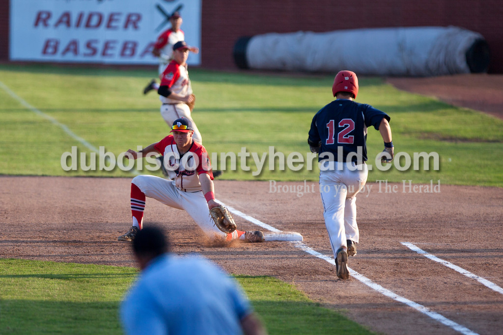Dubois County Bombers' Mark Giesler caught the ball at first, forcing out Owensboro Oilers Drew Bene during Wednesday night's Bombers game against the the Owensboro Oilers at League Stadium in Huntingburg. <br /> Alisha Jucevic/The Herald