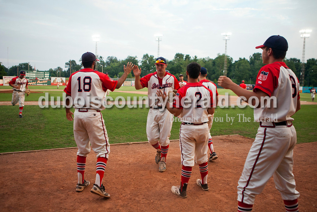 The Dubois County Bombers' high five Mark Giesler, center, as he ran in from the field during the second game of the league playoffs  on Saturday night at League Stadium in Huntingburg. The Hoptown Hoppers defeated the Dubois County Bombers 12-2. <br /> Alisha Jucevic/The Herald