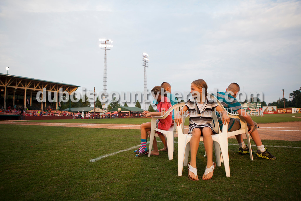 Savannah Nelson of Jasper, 9, center, looked toward the crowd as she waited for the song to begin again in musical chairs in between innings at the second game of the league playoffs at League Stadium on Saturday night in Huntingburg. The Hoptown Hoppers defeated the Dubois County Bombers 12-2. <br /> Alisha Jucevic/The Herald
