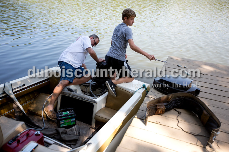 """Ariana van den Akker/The Herald<br /> Despite the low water level at Beaver Lake, Paul Jahn, left, and his grandson Drew Schneider, 13, both of Jasper, replaced the spark plugs on Jahn's boat on the lake in Jasper on Monday afternoon. Jahn, who has pledged money to reconstruct the spillway, said that he already had to reduce the height of his dock by a foot a few years ago because of the lower water levels. """"This place is a utopia out here for us,"""" Jahn said."""