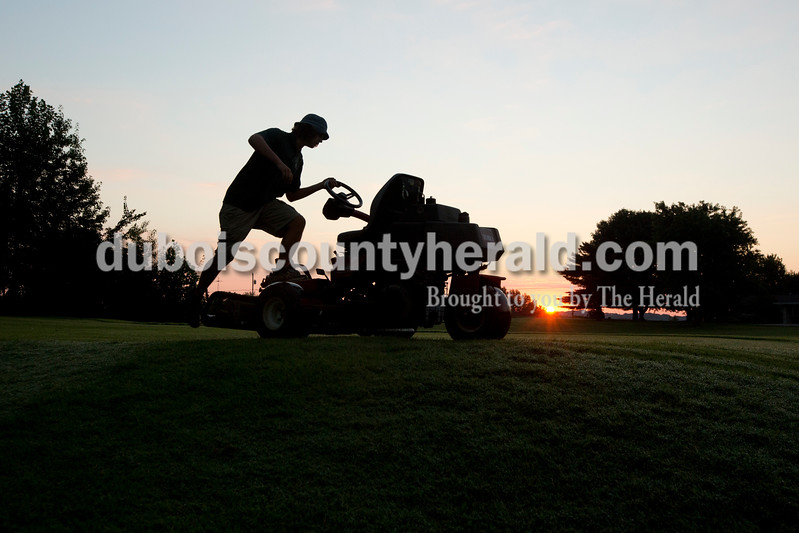 Derek Beckman of Jasper, 18, got back onto his mower after moving tee markers in the early morning hours of July 24 at Sultan's Run in Jasper. Before working at Sultan's Run, Beckman said he was not a morning person, but in the four years he's worked at the golf course, he's grown to love watching the sun rise as he works on maintaining the grounds. Beckman will be a freshman at  Indiana University-Purdue University Indianapolis this year.