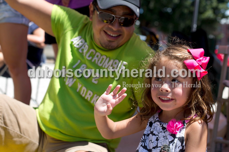 """Erica Lafser/The Herald<br /> Jose Hidalgo of Jasper took his daughter Mya, 5, to the Strassenfest parade on Sunday in Jasper. """"You wave hi and you smile,"""" Jose said to Mya."""