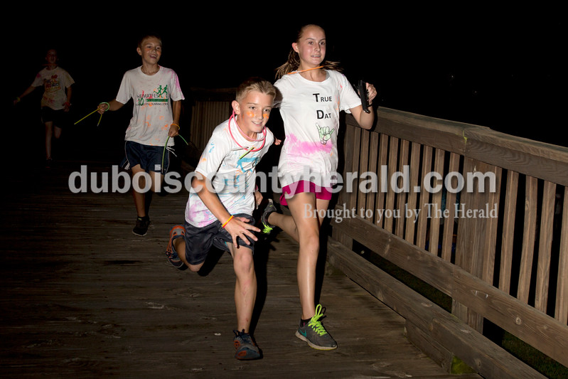 Erica Lafser/The Herald<br /> Mya Stiles of Jasper, 12, racesd her group member J.D. Kerber of Ferdinand, 11, center right, to the finish of the 2k glow run down the Jasper riverwalk that ended near Ruxer Golf Course, where a dance party was held directly afterwards on Wednesday night. The event was sponsored by Christian Church of Jasper and included participants from their middle and high school ministry. Layla Weyer of St. Anthony, 11, left, and Gabe Multer of Ferdinand, 11, followed right behind Stiles and Kerber. The four were in the same group.