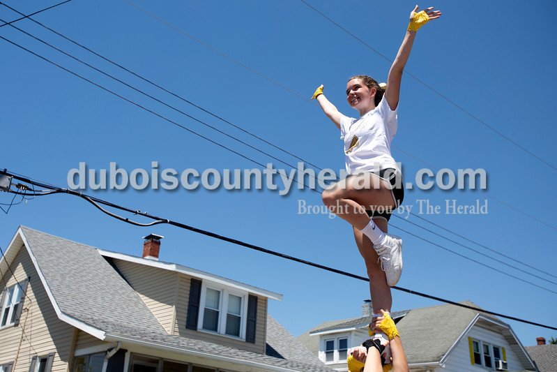 """Erica Lafser/The Herald<br /> Jasper High School cheerleader Emma Cave of Jasper, 16, was launched and held in the air by her teammates during the Strassenfest parade on Sunday in Jasper. """"My favorite part is making people smile with our tricks,"""" Cave said."""