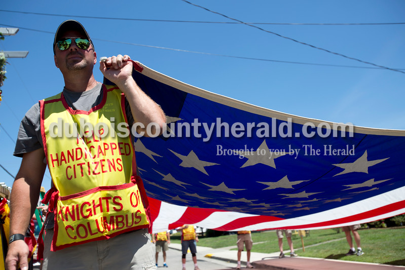 Erica Lafser/The Herald<br /> Tony Schmitt of Jasper walked with Jasper Knights of Columbus and threw Tootsie Rolls to audience members as he held the flag.
