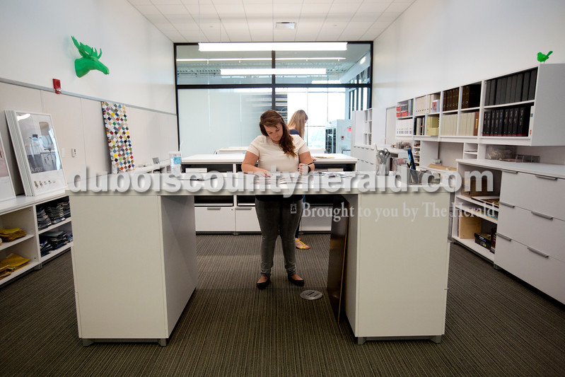 """Ariana van den Akker/The Herald<br /> Erica Neukam of Dubois, an interior design specialist, went through samples while working at National Office Furniture's new headquarters in Jasper on Thursday. The new headquarters, which has its grand opening on Saturday, incorporates the office into a """"working showroom."""""""