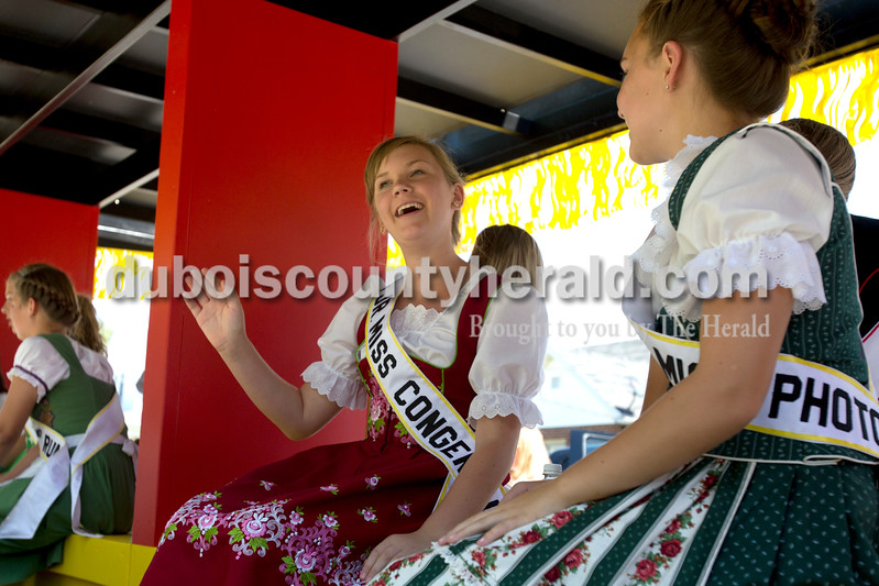 Erica Lafser/The Herald<br /> Jr. Miss Congeniality Caroline Prechtel of Jasper, 13, left, told Jr. Miss Photogenic Isabelle Blazey of Jasper, 13, right, about how they might have to switch arms they wave because they can get tired quickly during the Strassenfest parade on Sunday in Jasper.