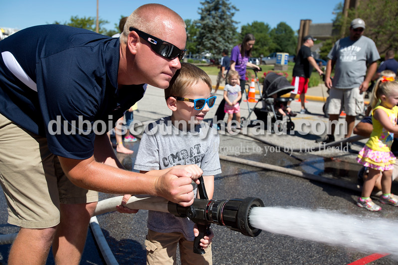Erica Lafser/The Herald<br /> Firefighter, Nathaniel Kern of Jasper, helped kids, like Ryan Metzger of Cincinatti, 4, pictured here, put out pretend fires during the junior firefighter challenge on Saturday as part of the Strassenfest celebrations. Metzger's father, Nick, grew up in Jasper.