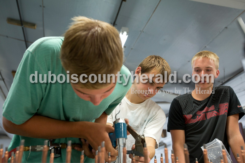 Erica Lafser/The Herald<br /> Kade Boeglin of Ferdinand, 16, left, attached the aluminum skin onto the horizontal stabilizer with the assistance and supervision of Dillon Hasenour of Ferdinand, 16, middle, and Jaxon Denu of Dubois, 17, right, during their time at the Huntingburg Airport program organized by Eric Seber of Jasper on Wednesday. The group has been meeting weekly since February to construct a Sonex aircraft that they hope will eventually be complete after some more fundraising for the rest of the building kit.
