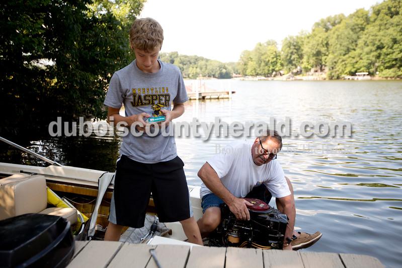 """Ariana van den Akker/The Herald<br /> Despite the low water level at Beaver Lake, Drew Schneider, 13, left, and his grandfather Paul Jahn, both of Jasper, replaced the spark plugs on Jahn's boat on the lake in Jasper on Monday afternoon. Jahn, who has pledged money to reconstruct the spillway, said that he already had to reduce the height of his dock by a foot a few years ago because of the lower water levels. """"This place is a utopia out here for us,"""" Jahn said."""