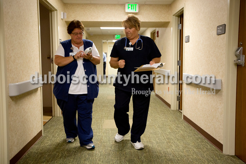 Ariana van den Akker/The Herald<br /> Janet Kemp of Huntingburg, right, checked in with RN Sharon Weisman of Dale in the inpatient rehabilitation unit at Memorial Hospital in Jasper on Friday. Kemp, who just started a job as a nurse at the hospital, went from having a well-paying job to homelessness a few years ago. She recently graduated with a degree in nursing with help from the VUJC Family Scholar House, which provides financial assistance and support for single parents going back to school.
