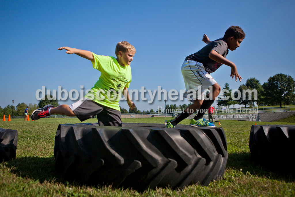 Carson May of Ferdinand, 9, and Brayden Piper of Santa Claus, 9, jumped over large tires during an obstacle course at the last day of summer camp on Tuesday afternoon at the Tri-County YMCA in Ferdinand.  <br /> Alisha Jucevic/The Herald
