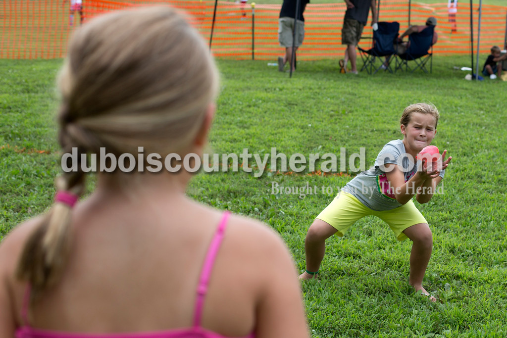 Erica Lafser/The Herald<br /> Ava Wicks of Elberfeld, 9, attempted to catch a water balloon thrown by Shae Bailey of Lynnville, 7, during a small competition at the annual Zoar Mosquito Fest on Saturday at Zoar United Methodist church and its picnic grounds in Holland.