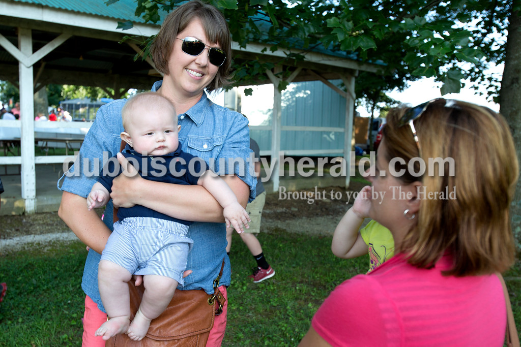 Erica Lafser/The Herald<br /> Erin Meyer of Holland held her friend's 5-month-old son, Tate Blessinger of Huntingburg, left, as she talked with Kelly Sherman of Huntingburg, whom held her 2-year-old daughter, Grace, right, during the annual Zoar Mosquito Fest on Friday at Zoar United Methodist church and its picnic grounds in Holland.