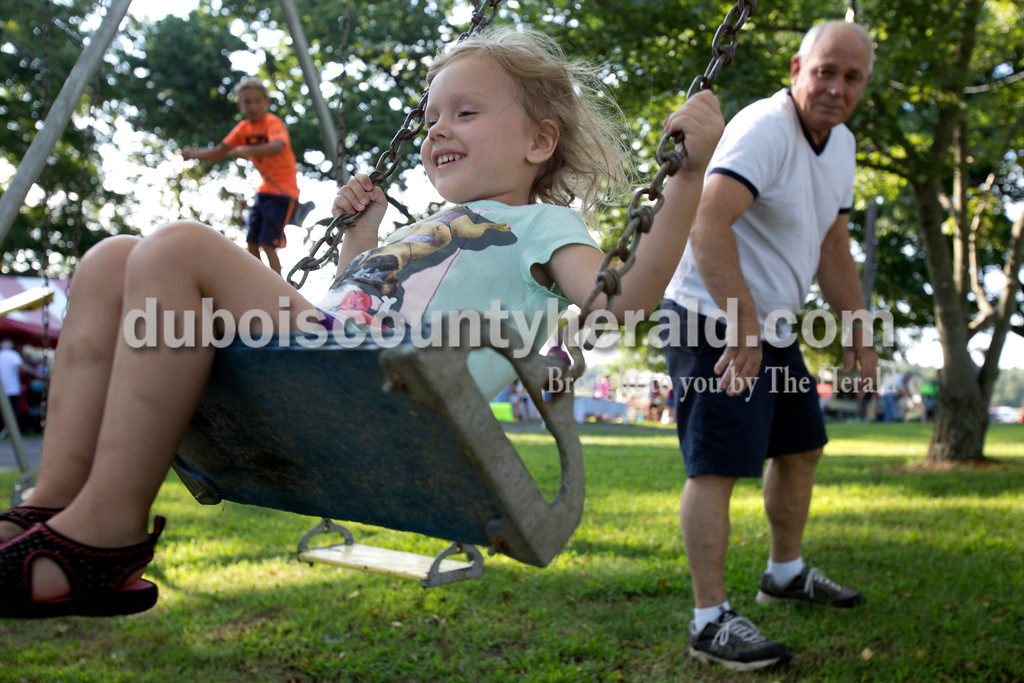 """Erica Lafser/The Herald<br /> Randy Flamion of Holland, right, pushed his granddaughter Amelia Kirk of Holland, 3, left, on the swings during the annual Zoar Mosquito Fest on Friday at Zoar United Methodist church and its picnic grounds in Holland. Flamion also pushed Kirk's cousin, William Flamion of Holland, 2, not pictured. """"It's hard to keep them both in the same place,"""" Randy said."""