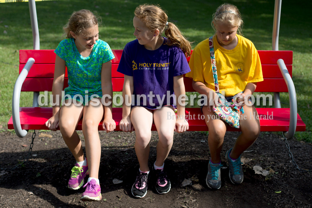 Erica Lafser/The Herald<br /> Braelyn Wehr of Ireland, 10, left, talked with Rachel Mehringer of Schnellville, 10, middle, and Grace Main of Jasper, 11, right, about their favorite boats at the cardboard boat regatta on Saturday at the Dave Buehler Plaza next to the Patoka River.