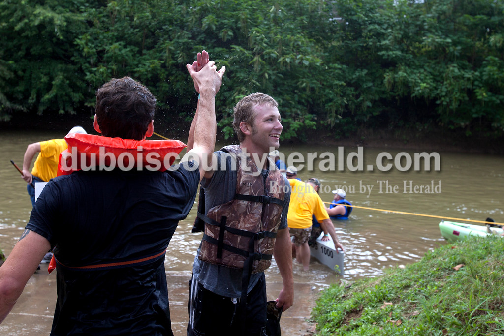 Erica Lafser/The Herald<br /> Aaron Wiles, left, high-fived Ryan Fierst, right, both of Jasper and on the Herald's regatta team, after the entertaining corporate championship race in the annual Holy Trinity Cardboard Regatta on Saturday in Patoka River next to the Dave Buehler Plaza in Jasper.