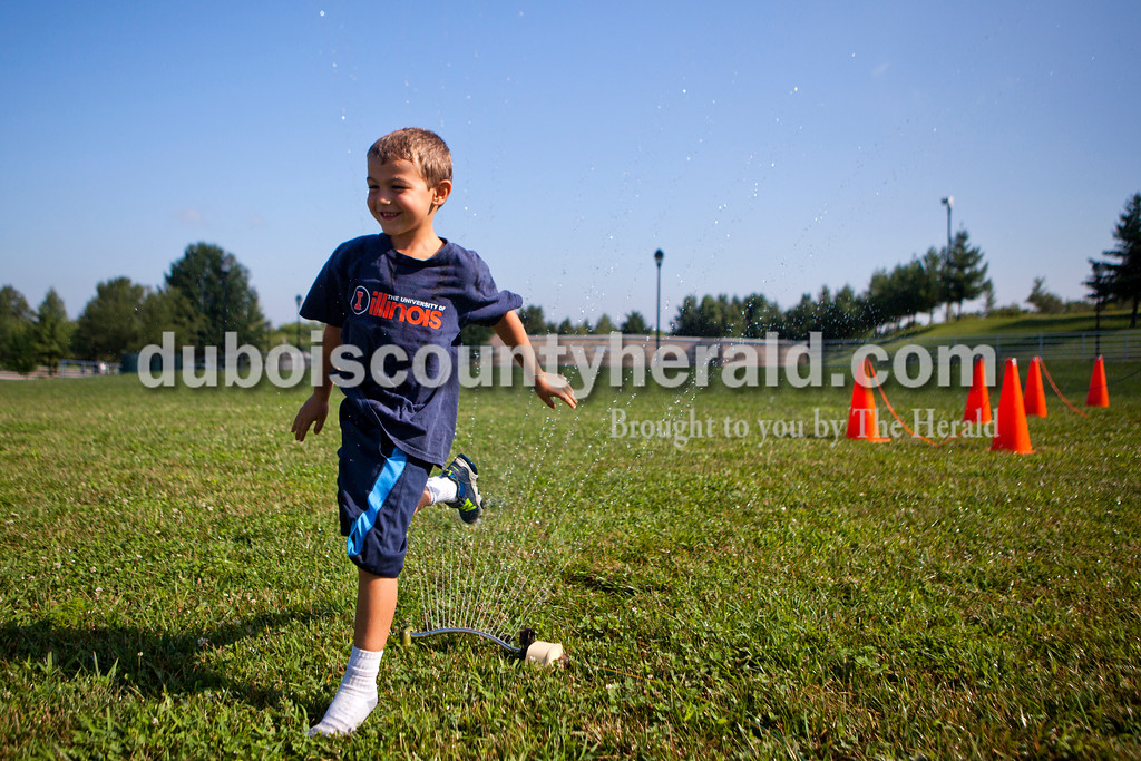 Jeremiah Marx of Ferdinand, 6, leapt through a sprinkler at the end of an obstacle course during the last day of summer camp on Tuesday afternoon at the Tri-County YMCA in Ferdinand.  <br /> Alisha Jucevic/The Herald