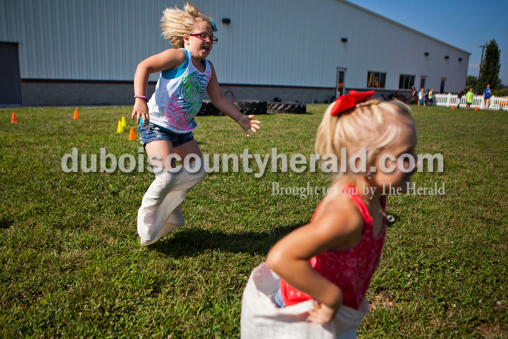 Bailee Eckert, 9, and her sister and Allison Eckert, 6, both of Santa Claus hopped across the grass in an obstacle course during the last day of summer camp on Tuesday afternoon at the Tri-County YMCA in Ferdinand.  <br /> Alisha Jucevic/The Herald