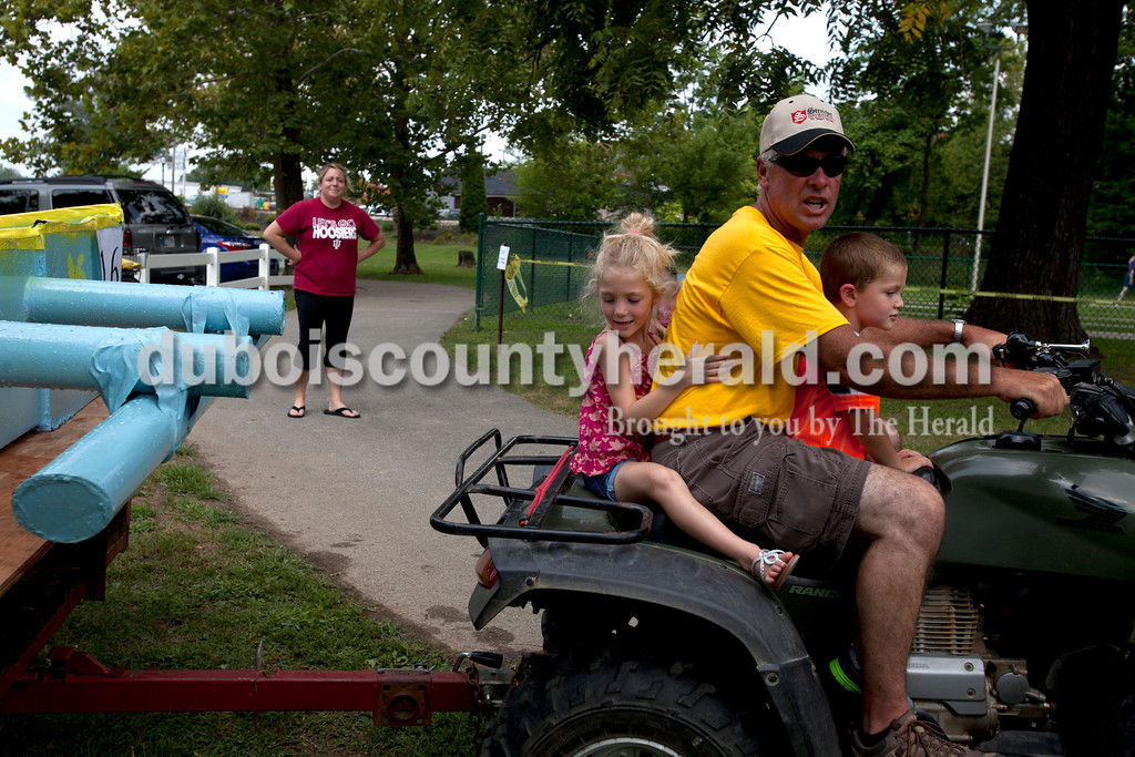 Erica Lafser/The Herald<br /> Kylie Mehringer of Jasper, 4, and her brother Caleb, 3, rode with Brian Mundy of Jasper, a family friend, on a tractor while they pulled the boats from the Holy Trinity Cardboard Regatta on Saturday in the Patoka River next to the Dave Buehler Plaza in Jasper.