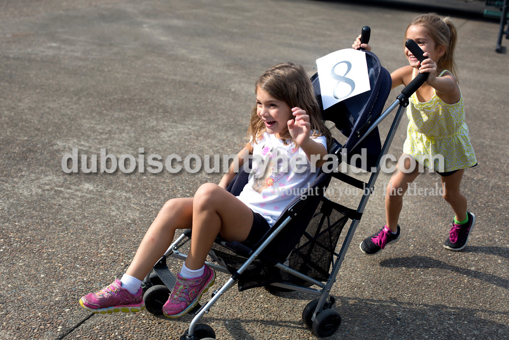 Erica Lafser/The Herald<br /> Kaelyn Sternberg of Jasper, 7, pushed her friends Brynlee Wehr of Jasper, 6, in a stroller as fast as she could around the Dave Buehler Plaza next to the Patoka River on Saturday before the cardboard boat regatta took place in the river.