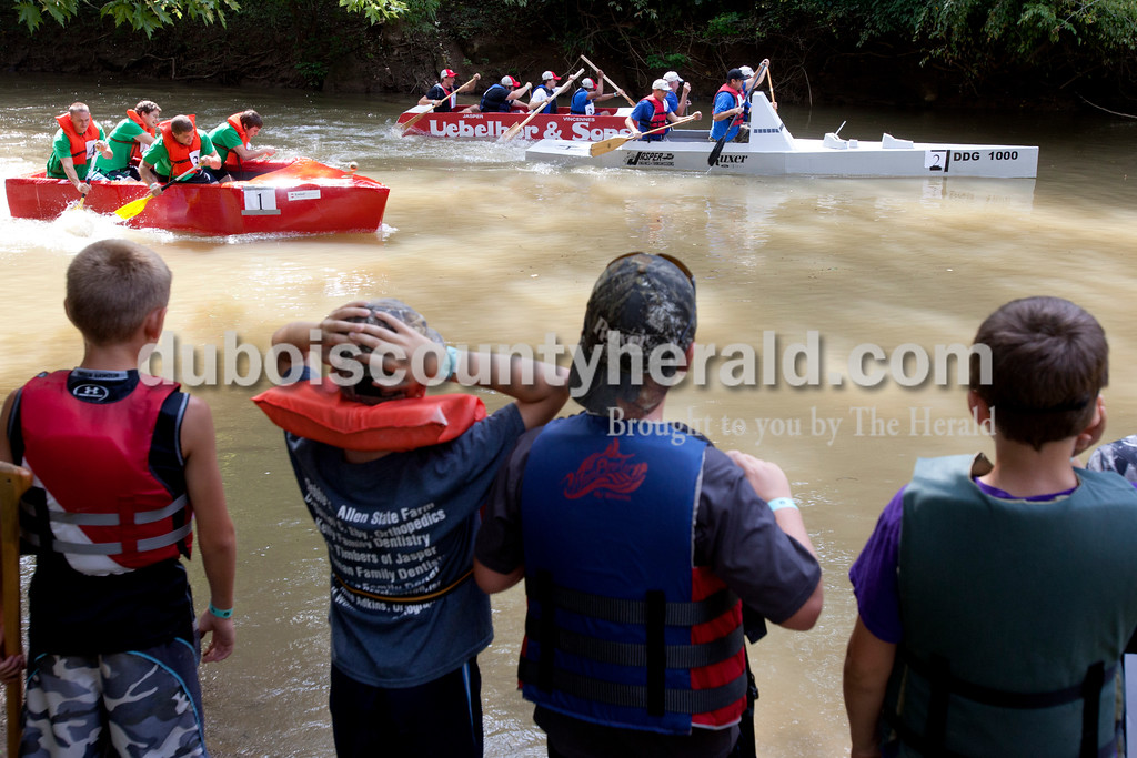 Erica Lafser/The Herald<br /> Young boys watched a corporate race between Kimball Electronics, left, Uebelhor and Sons, middle, and Jasper Engines and Transmissions Ruxer Ford Lincoln, right, during the Holy Trinity Cardboard Regatta on Saturday in Patoka River next to the Dave Buehler Plaza in Jasper.