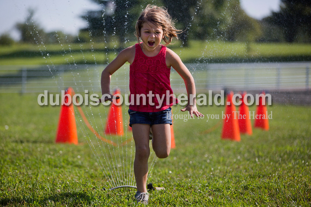 Lilly Gogel of New Boston, 5, sprinted  through a sprinkler at the end of an obstacle course outside of the Tri-County YMCA on Tuesday morning in Ferdinand.  <br /> Alisha Jucevic/The Herald