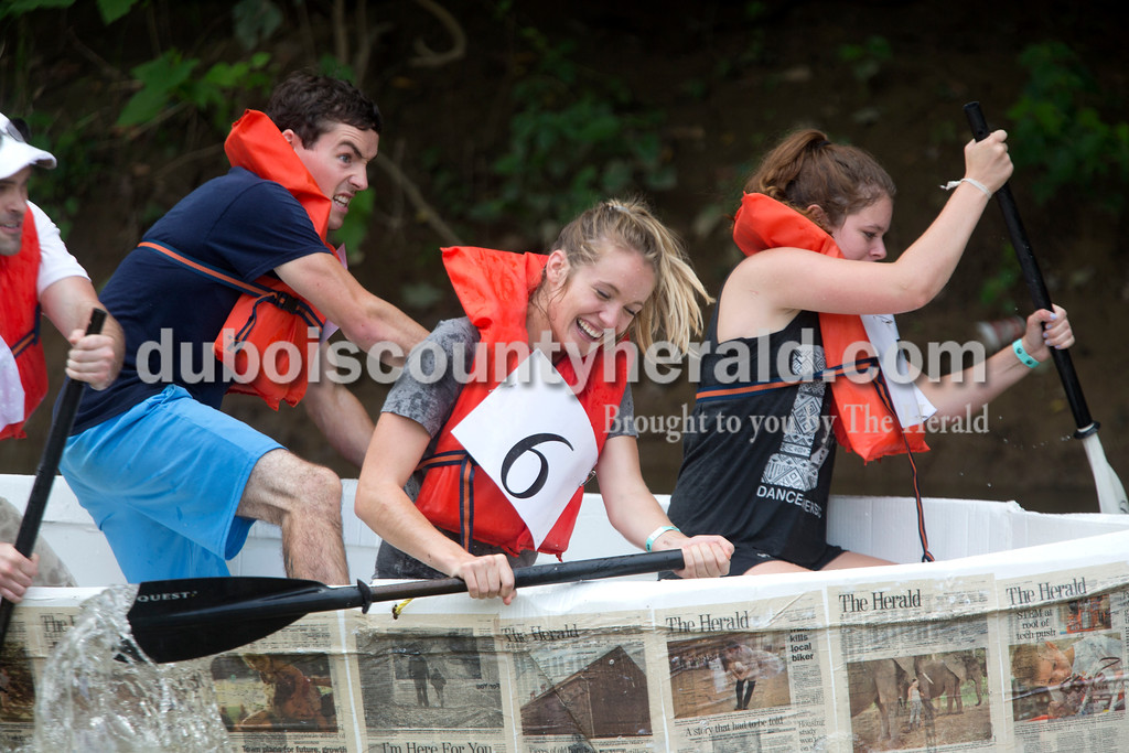 Erica Lafser/The Herald<br /> Aaron Wiles, left, Alisha Jucevic, middle, and Cassie Heeke, right, all of Jasper, paddled to the finish of a preliminary race in the Herald's cardboard boat during the Holy Trinity Cardboard Regatta on Saturday in Patoka River next to the Dave Buehler Plaza in Jasper.
