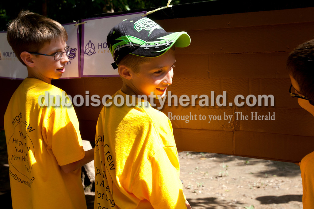 Erica Lafser/The Herald<br /> Abe Eckman of Jasper, 11, left, and Luke Hasenour of St. Anthony, 11, right, were a part of the Holy Trinity Cardboard Regatta Crew on Saturday for the annual Holy Trinity Cardboard Regatta fundraiser in Patoka River next to the Dave Buehler Plaza. Eckman and Hasenour helped carry the boats into the river.