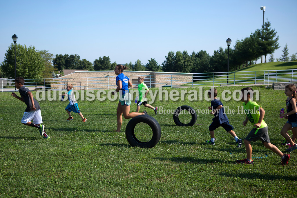 """YMCA Healthy Living Coordinator Brittney Heise ran across the grass with her summer campers during the last day of camp on Tuesday morning at the Tri-County YMCA in Ferdinand. """"I wanted to take them outside,"""" Haise said. """"Give them a chance to enjoy the last day of summer.""""<br /> Alisha Jucevic/The Herald"""