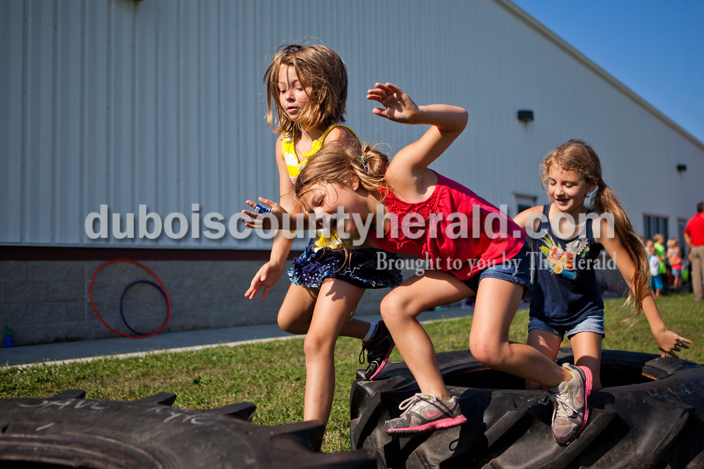 With the first day of school right around the corner, YMCA Healthy Living Coordinator Brittney Heise, decided to make the last day of summer camp a memorable one. Kendall King of St. Meinrad, 8, Lilly Gogel of New Boston, 5, and Ella Gogel of New Boston, 7, scrambled over large tires in an obstacle course that Haise had set up on Tuesday morning at the Tri-County YMCA in Ferdinand.  <br /> Alisha Jucevic/The Herald