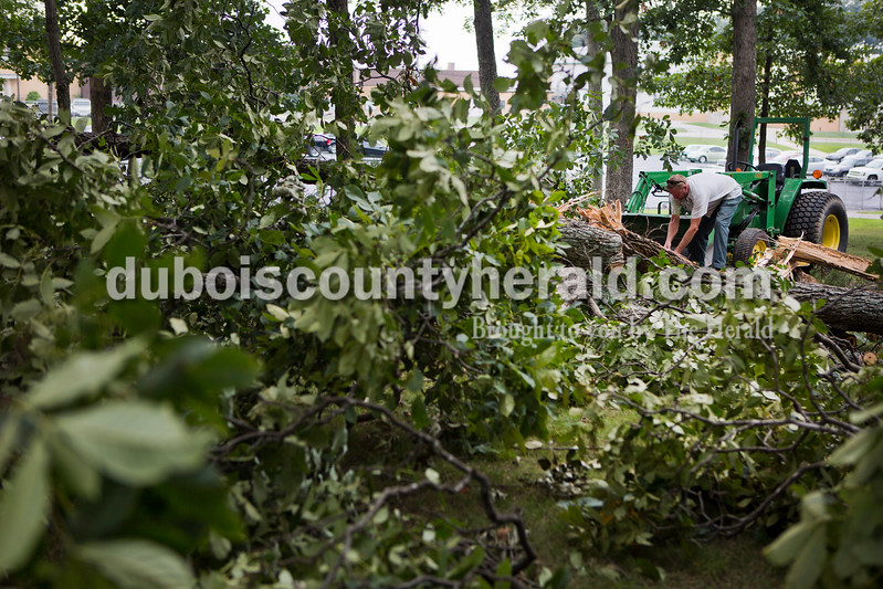 """Forest Park High School maintenance worker, Scott Hoffman, cleared fallen trees by the high school tennis courts on Monday afternoon in Ferdinand. """"All the little limbs are blown everywhere,"""" Hoffman said. Three trees fell on the campus near the tennis courts and one tree fell by the high school baseball field. <br /> Alisha Jucevic/The Herald"""