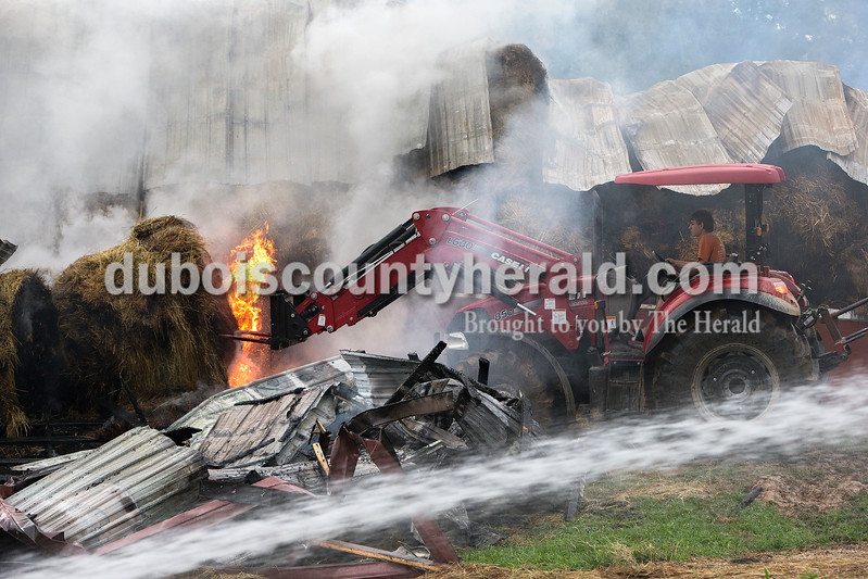 Austin Rothgerber of Kyana pulled hay bales from a barn that was destroyed by fire this morning near on his family's property this morning. Dave Weatherwax/The Herald
