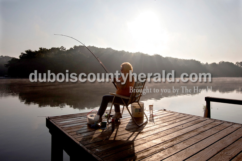 Dave Weatherwax/The Herald<br /> Nancy Herzog of Jasper set the hook on her first fish of the morning as she fished from a dock on Beaver Lake on Wednesday. Herzog used to own a cabin directly across the lake from where she was fishing and said she still enjoys spending much of her free time fishing on the lake.