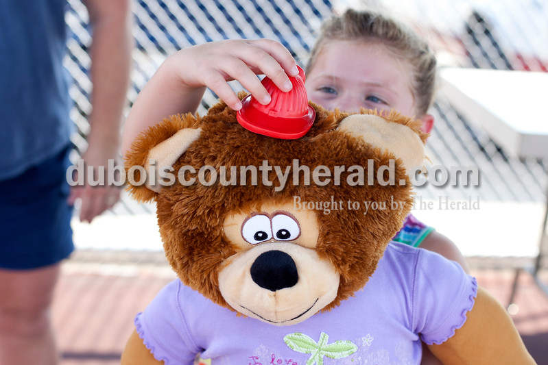 Erica Lafser/The Herald<br /> Ava Gehlhausen of Jasper, 5, put her fireman hat on her bear; both were prizes Gehlhausen won from activities during the St. Anthony Firemen's Fest at the St. Anthony Community Center on Saturday in St. Anthony.
