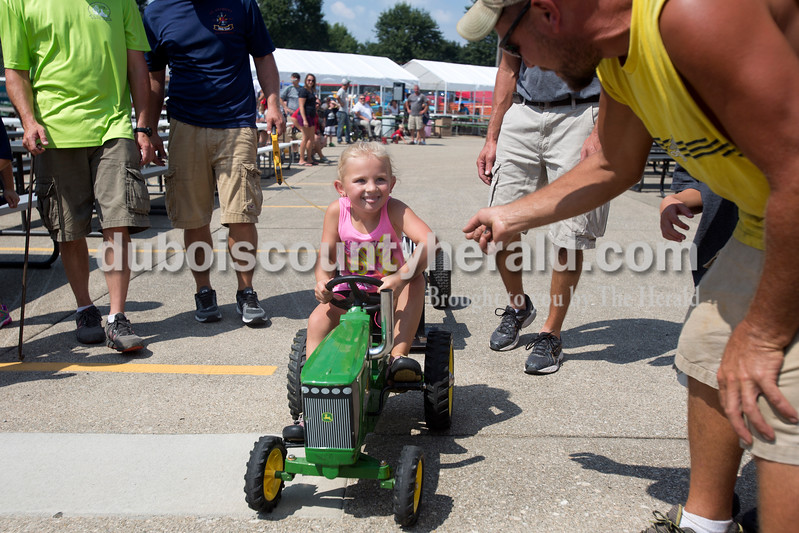 """Erica Lafser/The Herald<br /> Adison Andry of Birdseye, 5, pedaled her hardest and looked up to her father, Todd, during the St. Anthony Firemen's Fest at St. Anthony Community Center on Saturday in St. Anthony while he cheered her on. """"She told me when she woke up today, """"dad, I'm winning first place today,"""""""" Todd said."""